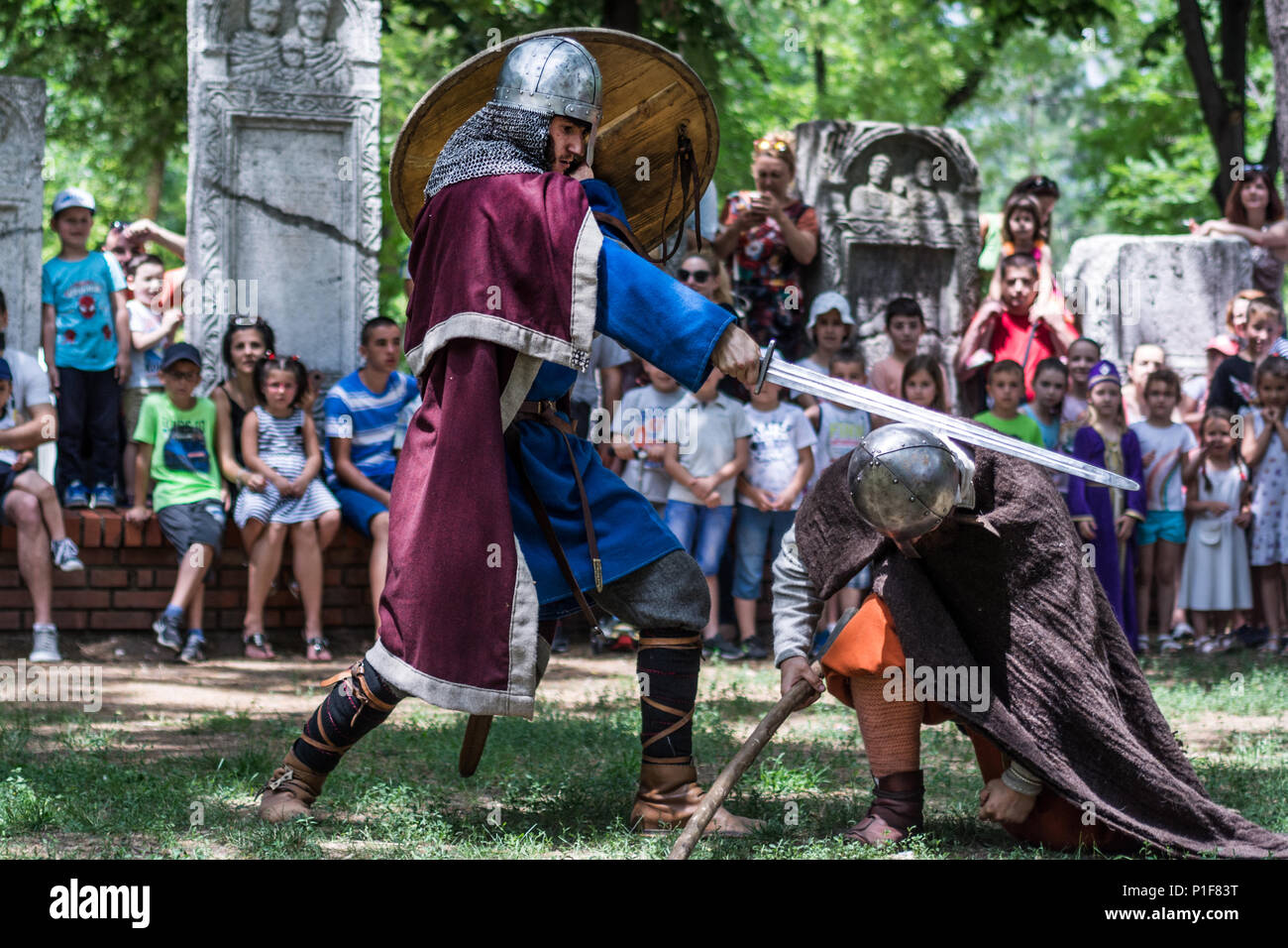Nis, Serbia - June 10, 2018: Medieval knight with armor and swords fighting in nature on tournament and public watching. Middle ages battle concept Stock Photo