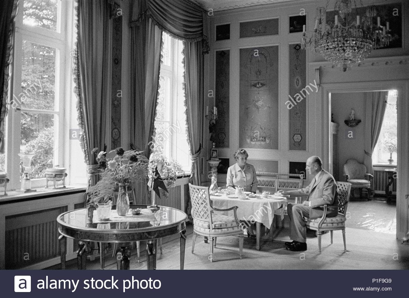 Mr. and Mrs. Essberger dining in their Hamburg townhouse, built in 1790 by Hansen, the architect who built most of Copenhagen. Mr. Essberger is one of Hamburg's wealthiest shipowners. Hamburg,1958. Location: Townscape, Hamburg, Germany. - Stock Image