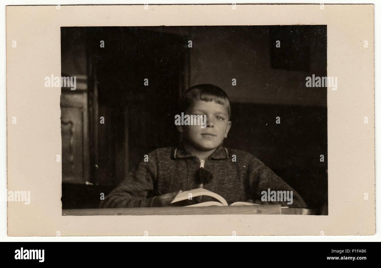 EILENBURG, GERMANY - CIRCA 1950s: Vintage photo shows pupil boy with book at the desk. Black & white retro photo. Stock Photo