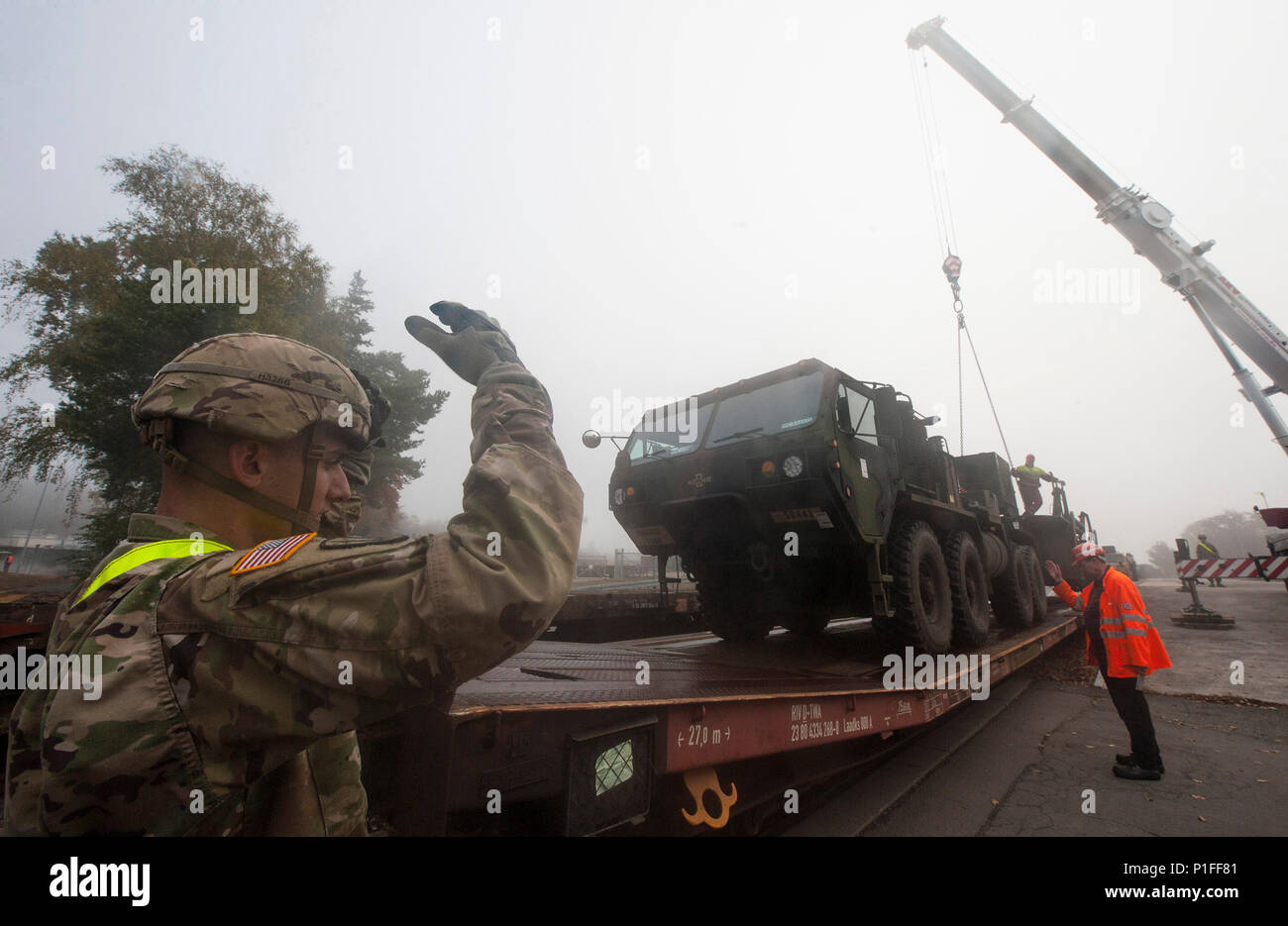 """U.S. Army Sergeant Joseph Harris (left), with the 5th Battalion, 7th Air Defense Artillery Regiment, directs the loading of a military support vehicle onto a railroad flatbed trailer at Rhine Ordnance Barracks in Kaiserslautern, Germany on Oct. 27, 2016. The military transport is in preparation for the 10th Army Air Missile Defense Command's """"Patriot Shock"""" exercise set to happen in Romania over the next several weeks. (DoD News photo by Tech. Sgt. Brian Kimball) - Stock Image"""