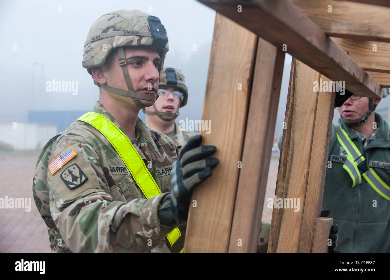 """U.S. Army Sergeant Joseph Harris, with the 5th Battalion, 7th Air Defense Artillery Regiment, unloads wooden support systems during a vehicle transport operation at Rhine Ordnance Barracks in Kaiserslautern, Germany on Oct. 27, 2016. The military transport is in preparation for the 10th Army Air Missile Defense Command's """"Patriot Shock"""" exercise set to happen in Romania over the next several weeks. (DoD News photo by Tech. Sgt. Brian Kimball) - Stock Image"""