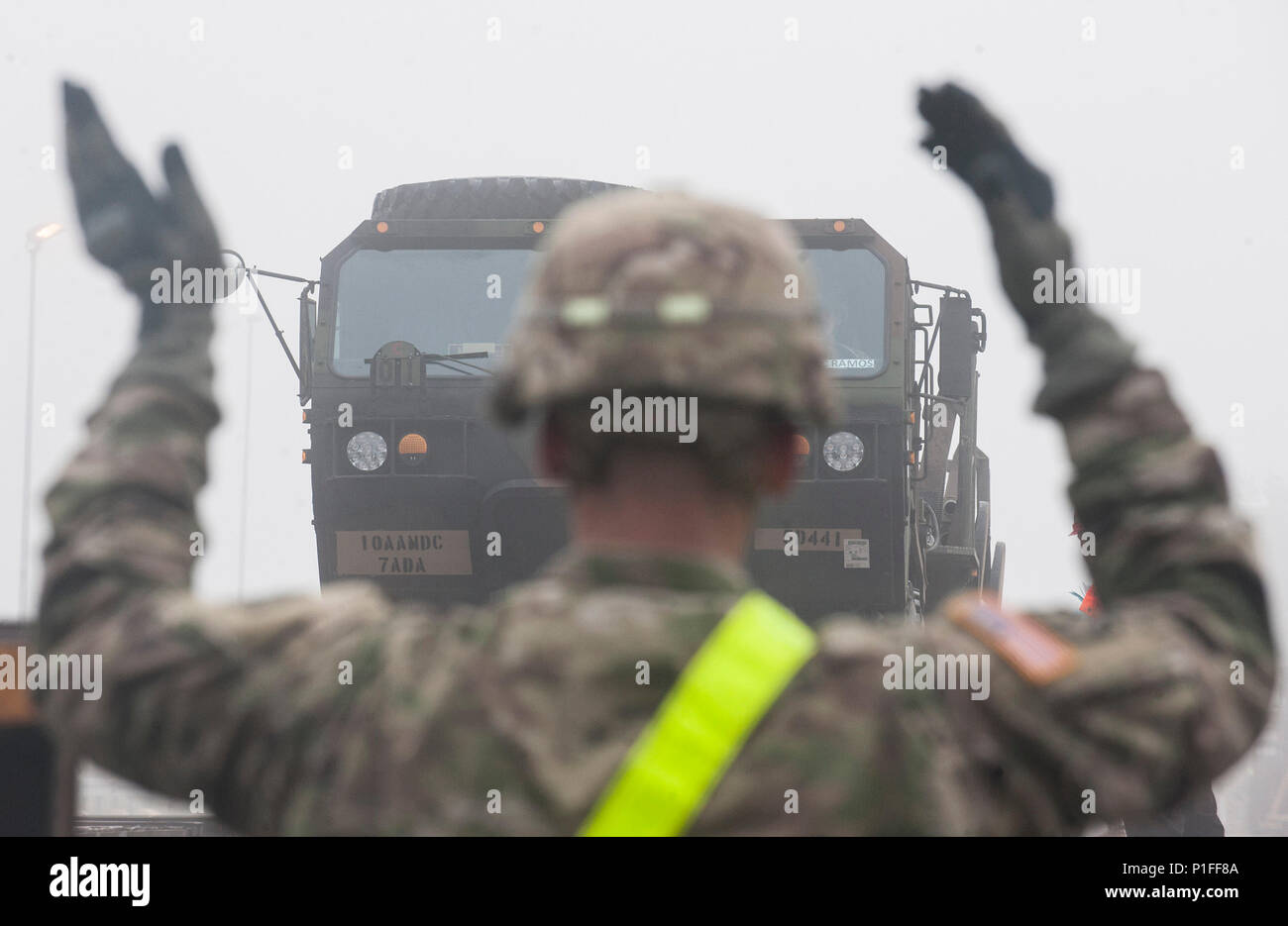 """U.S. Army Sergeant Joseph Harris, with the 5th Battalion, 7th Air Defense Artillery Regiment, directs the loading of a military support vehicle onto a railroad flatbed trailer at Rhine Ordnance Barracks in Kaiserslautern, Germany on Oct. 27, 2016. The military transport is in preparation for the 10th Army Air Missile Defense Command's """"Patriot Shock"""" exercise set to happen in Romania over the next several weeks. (DoD News photo by Tech. Sgt. Brian Kimball) - Stock Image"""