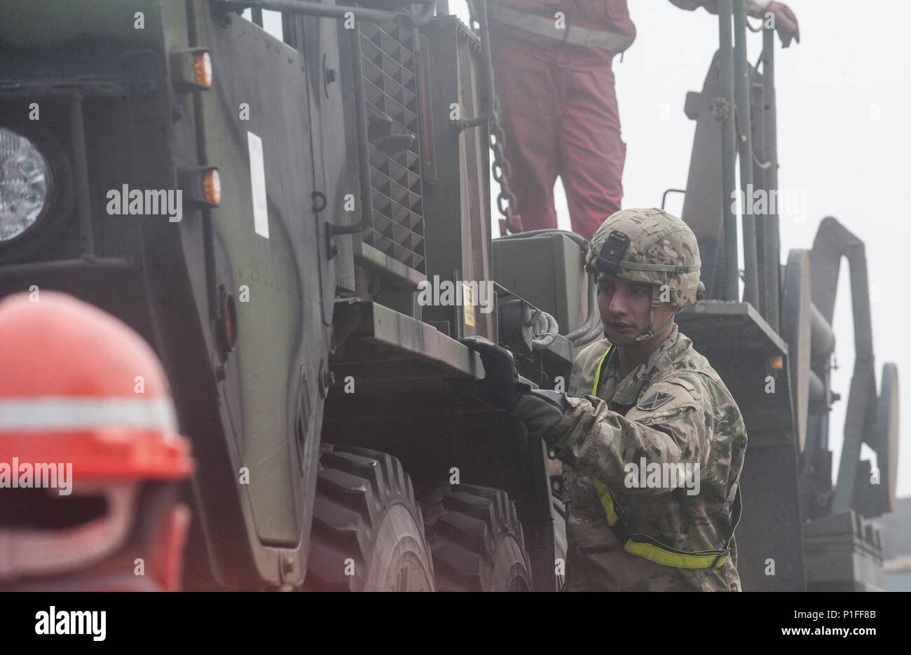 """U.S. Army Sergeant Joseph Harris, with the 5th Battalion, 7th Air Defense Artillery Regiment, assists in loading military support vehicles onto a railroad flatbed trailer at Rhine Ordnance Barracks in Kaiserslautern, Germany on Oct. 27, 2016. The military transport is in preparation for the 10th Army Air Missile Defense Commands """"Patriot Shock"""" exercise set to happen in Romania over the next several weeks. (DoD News photo by Tech. Sgt. Brian Kimball) - Stock Image"""