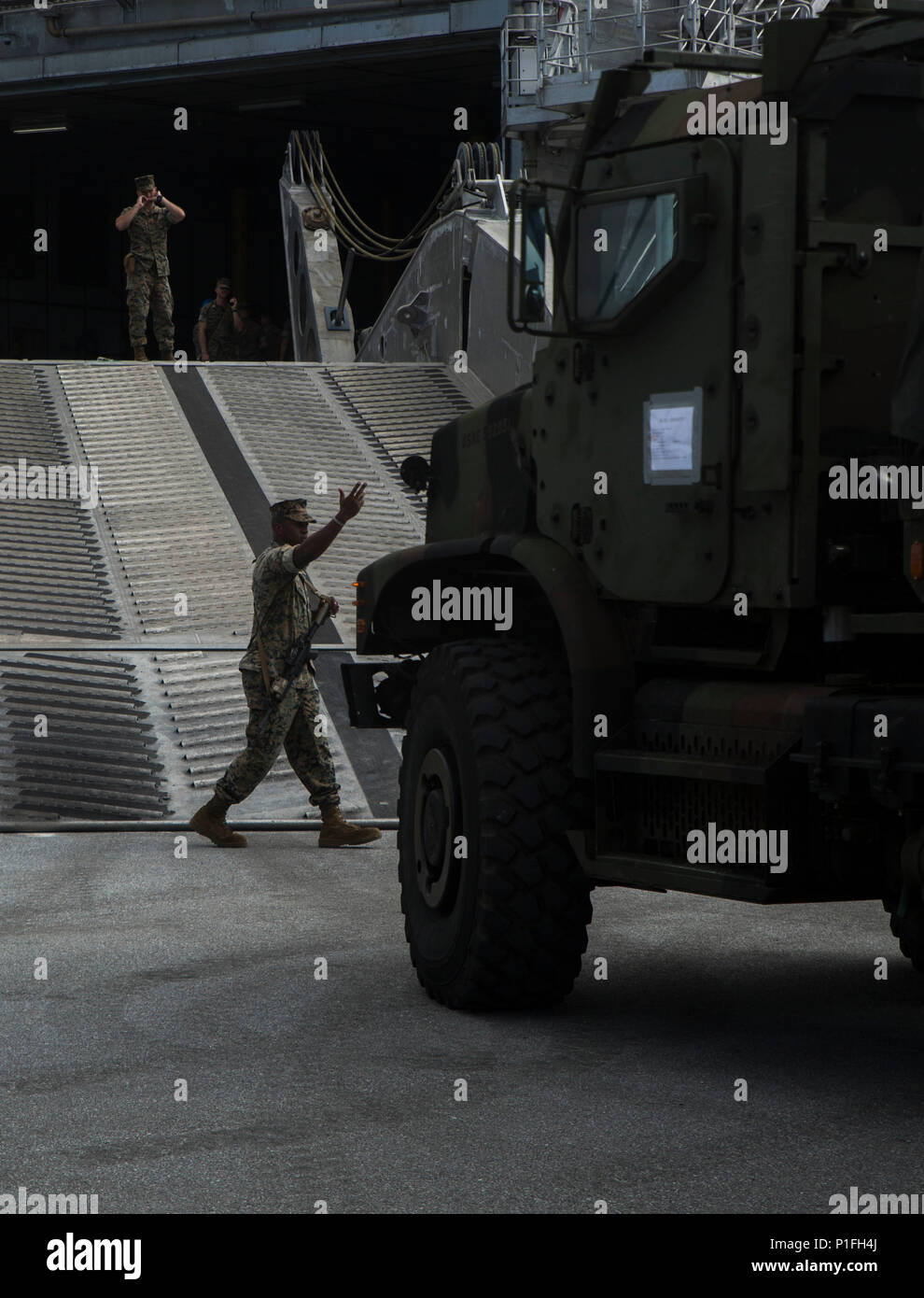 Sgt. Jeremaine Craighead, from Alexandria, Virginia, guides a 7-ton truck on to the USNS Fall River (T-EPF-4)  at Naha Port, Okinawa, Japan, during Blue Chromite 2017, October 28, 2016. Blue Chromite is a U.S. –only exercise which strengthens the Navy-Marine Corps expeditionary, amphibious rapid-response capabilities based in Okinawa and greater Indo-Asia-Pacific region. Craighead is a motor transportation operator with Truck Company, 3rd Marine Division, Headquarters Battalion, III Marine Expeditionary Force. (U.S. Marine Corps photo by Lance Cpl. Kelsey Dornfeld/ Released) - Stock Image
