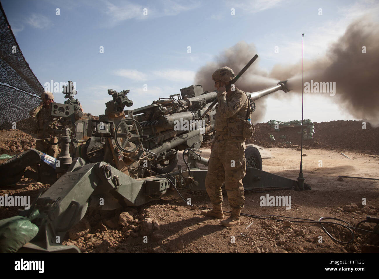U.S Army Soldiers, Battery C, 1st Battalion, 320th Field Artillery Regiment, 101st Airborne Division, fire a M777 towed 155 mm howitzer at Platoon Assembly Area 14, Iraq, in support of Combined Joint Task Force-Operation Inherent Resolve (CJTF-OIR), Oct. 21, 2016.  CJTF-OIR is a multinational effort to weaken and destroy Islamic State in Iraq and the Levant operations in the Middle East region and around the world. (U.S. Army photo by Sgt. Joshua Wooten) - Stock Image