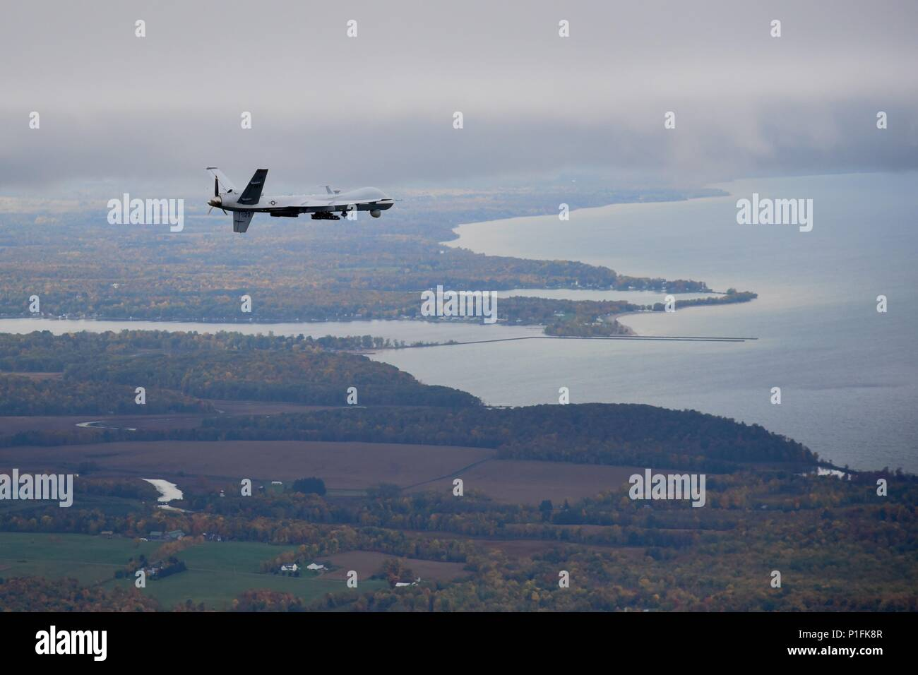 Syracuse, NY – A remotely piloted MQ-9 Reaper operated by the New York Air National Guard's 174th Attack Wing flies a routine training mission over Central New York on October 23, 2016. The Civil Air Patrol provides chase plane operations for the MQ-9, to and from restricted air space, to meet FAA see-and-avoid requirements of remotely piloted aircraft (RPA). (U.S. Air National Guard Photo by Master Sgt. Eric Miller/released) - Stock Image