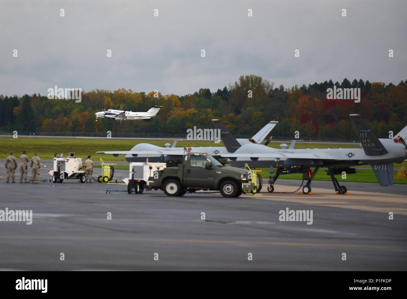 Syracuse, NY – Members of the 174th Attack Wing Maintenance Group prepare to launch remotely piloted MQ-9 Reapers for a routine training  mission on October 23, 2016. The MQ-9 is a long-endurance aircraft whose primary mission is to provide real-time intelligence, surveillance and reconnaissance (ISR) to military ground commanders. (U.S. Air National Guard Photo by Master Sgt. Eric Miller/released) - Stock Image