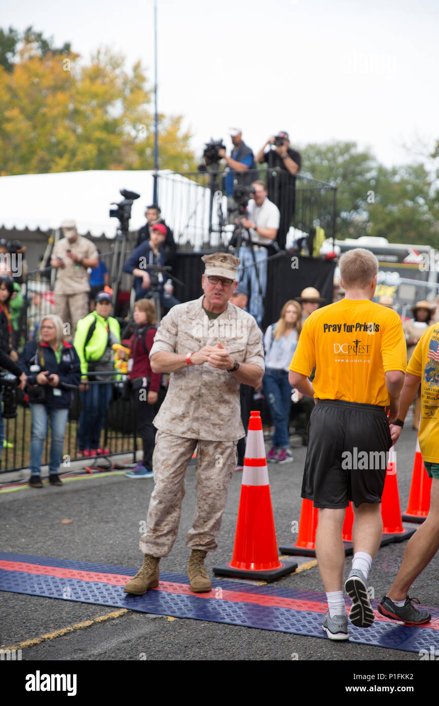 U.S. Marine Corps Maj. Gen. John J. Broadmeadow, commanding general, Marine Corps Installations Command cheers on runners at the finish line of the 41st Marine Corps Marathon, Arlington, Va., Oct. 30, 2016. Also known as 'The People's Marathon,' the 26.2 mile race drew roughly 30,000 participants to promote physical fitness, generate goodwill in the community, and showcase the organizational skills of the Marine Corps. (U.S. Marine Corps photo by Sgt. Alexandria Blanche) - Stock Image
