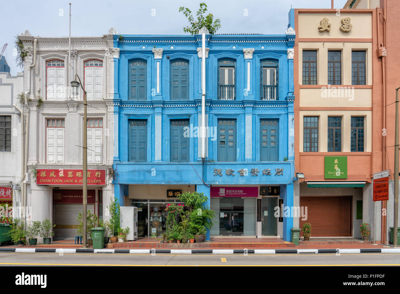 Singapore - June 10, 2018: Colorful Shophouses in Chinatown with closed shoppes - Stock Image