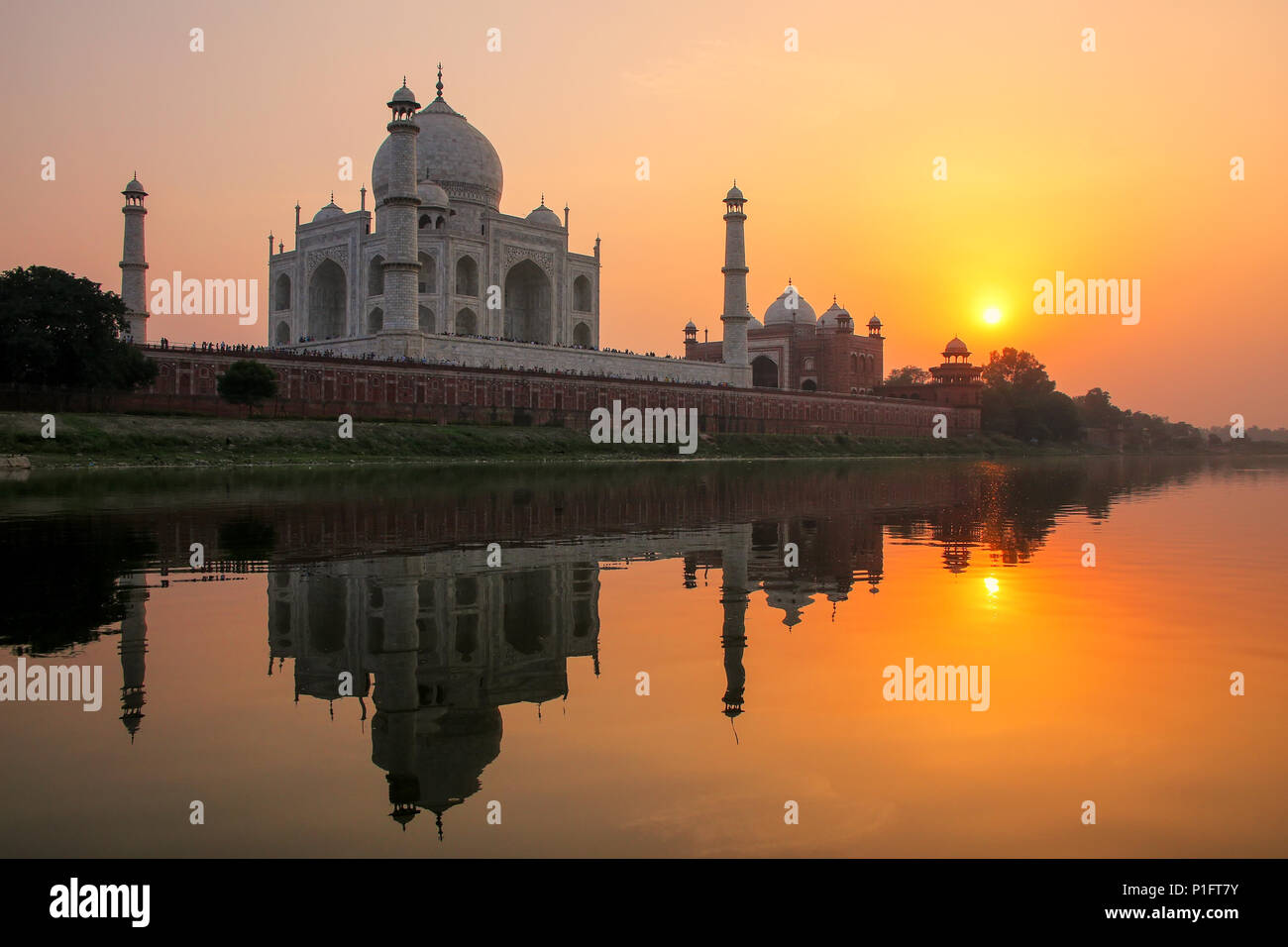 Taj Mahal reflected in Yamuna river at sunset in Agra, India. It was commissioned in 1632 by the Mughal emperor Shah Jahan to house the tomb of his fa - Stock Image