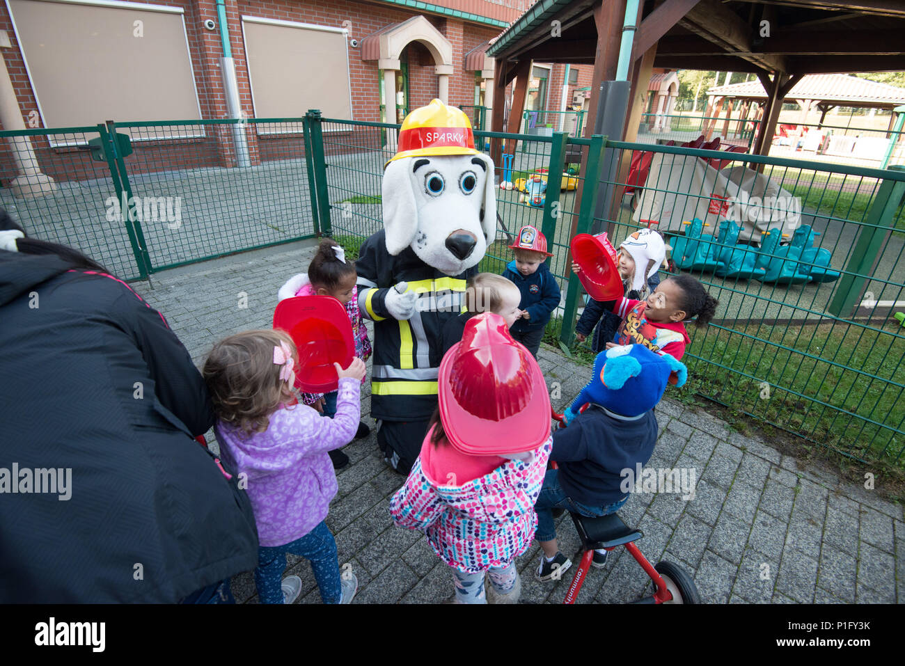 Sparky the fire dog socializes with children with U.S. Army Benelux SHAPE Child Development Center after a fire drill during fire prevention week, at SHAPE, in Mons, Belgium, Oct. 13, 2016. (U.S. Army photo by Visual Information Specialist Pierre-Etienne Courtejoie) - Stock Image