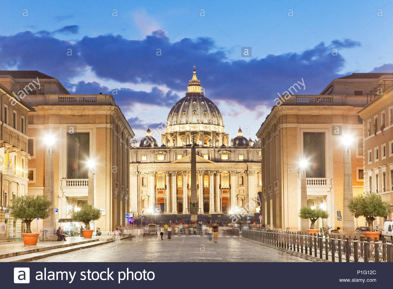 Italy, Rome, St. Peter's Basilica and Dome seen from Via della Conciliazione illuminated at dusk - Stock Image