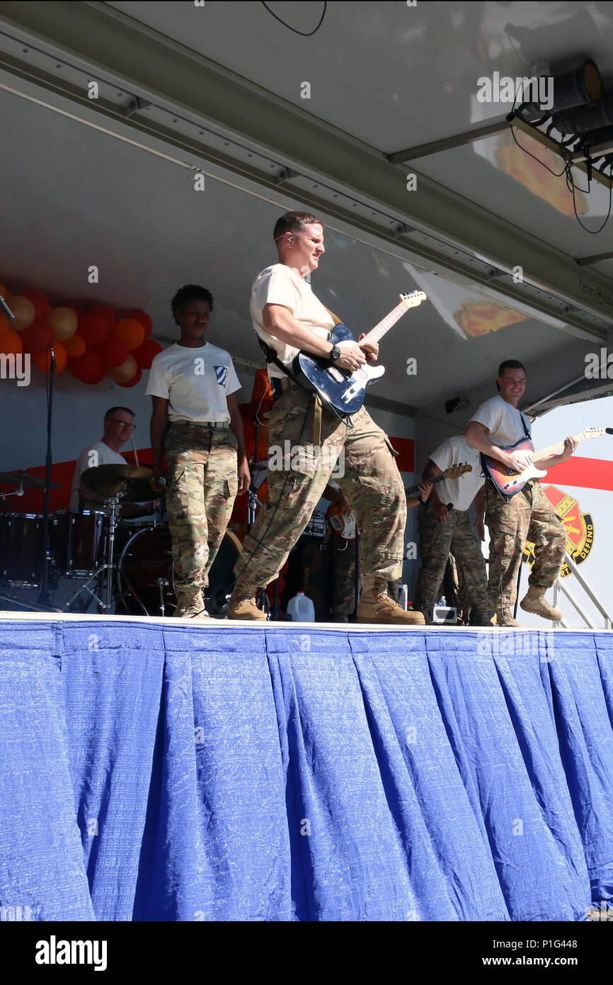Audie Murphie's Mixtape, comprised of members of the 3rd Infantry Division band, play rock music for attendees at the 11th annual Liberty County YMCA Fall Festival in Hinesville, Ga., October 29, 2016. In attendance were engineers from Bravo Company, 9th Brigade Engineer Battalion, 2nd Infantry Brigade Combat Team, 3rd ID, and 3rd ID mascot, Sgt. Rocky. (U.S. Army photo by Spc. Efren Rodriguez/release) - Stock Image