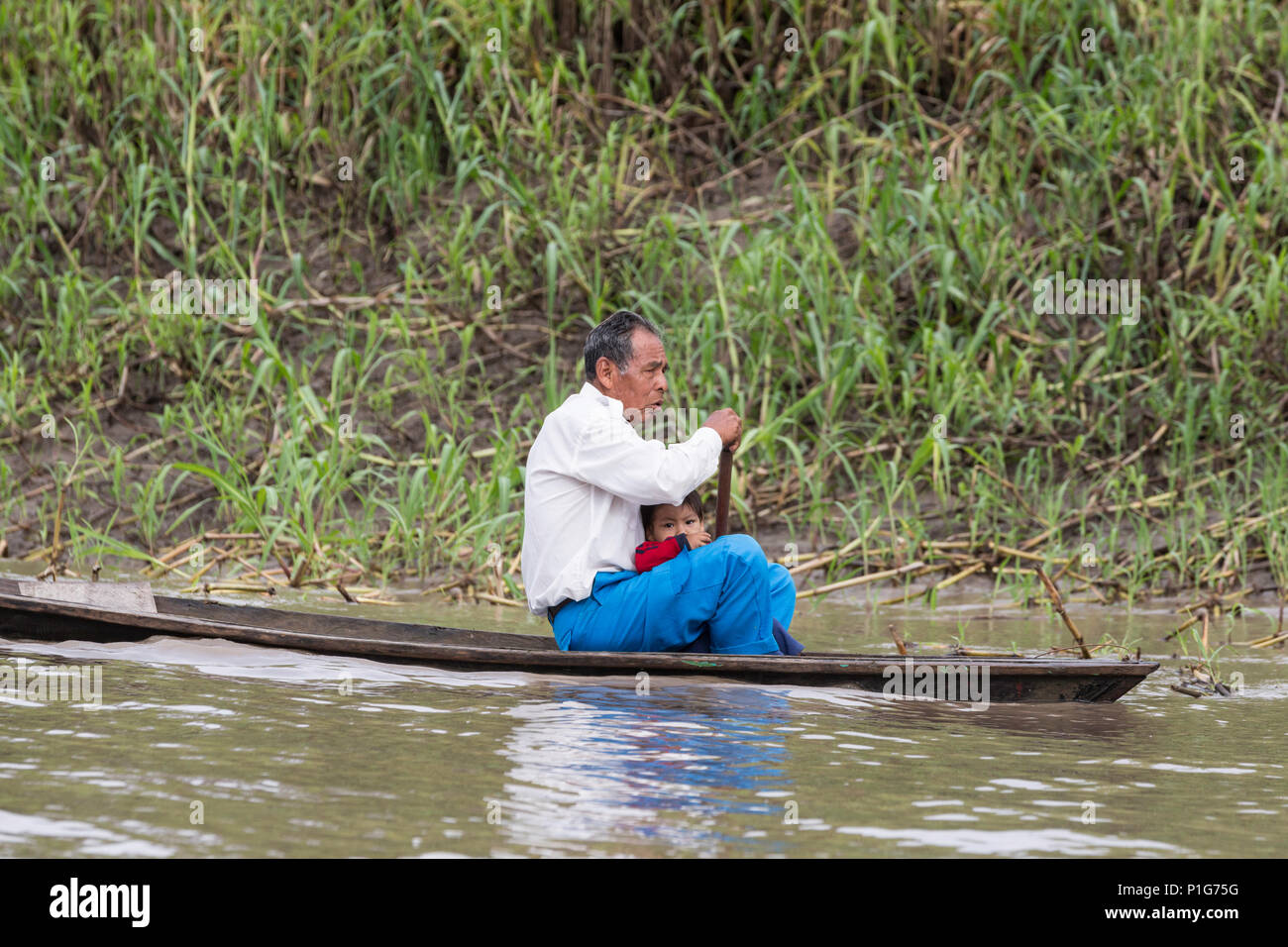 Man paddling dugout canoe, Puerto Miguel, Upper Amazon River Basin, Loreto, Peru - Stock Image