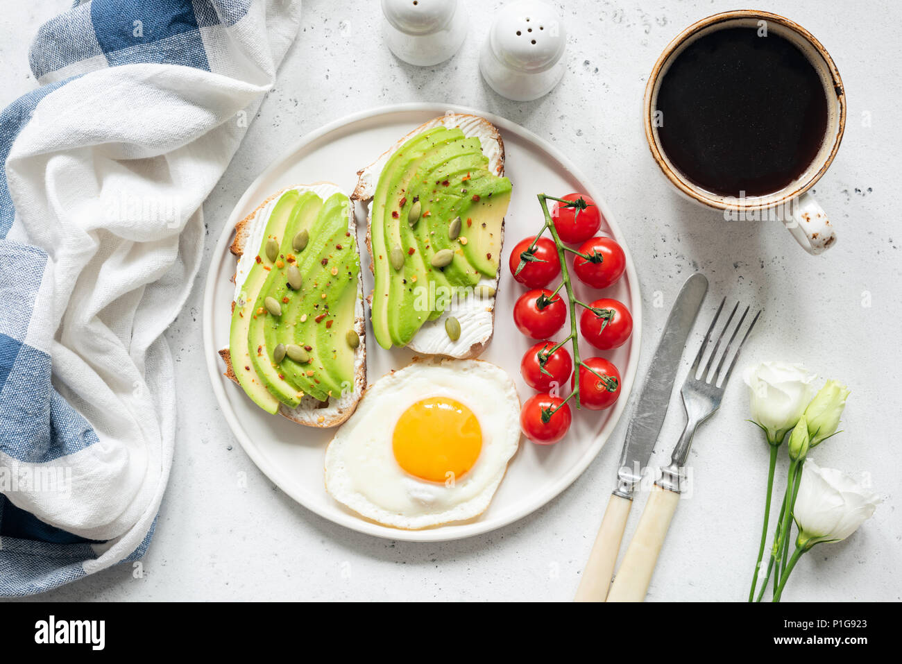 Breakfast avocado toast with fried egg, cherry tomatoes, cup of coffee and white flowers. Breakfast in bed. Healthy lifestyle, healthy eating concept - Stock Image