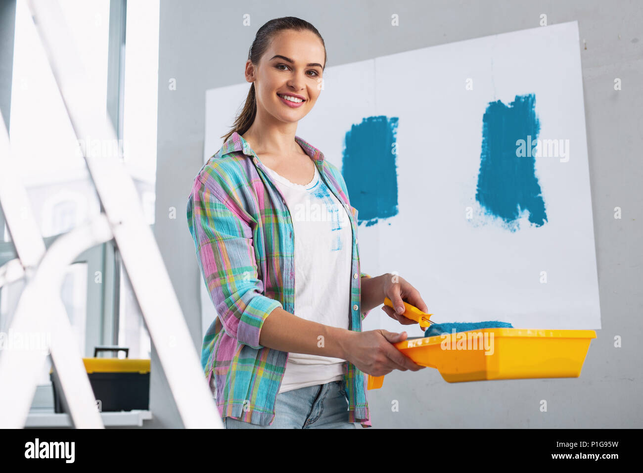 Cheerful girl doing some renovations in her flat - Stock Image