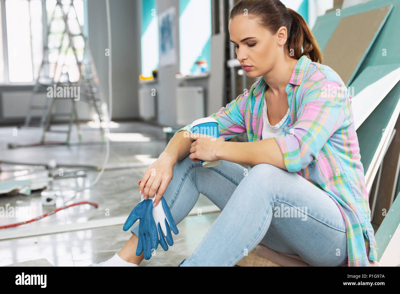 Exhausted young woman having a break - Stock Image
