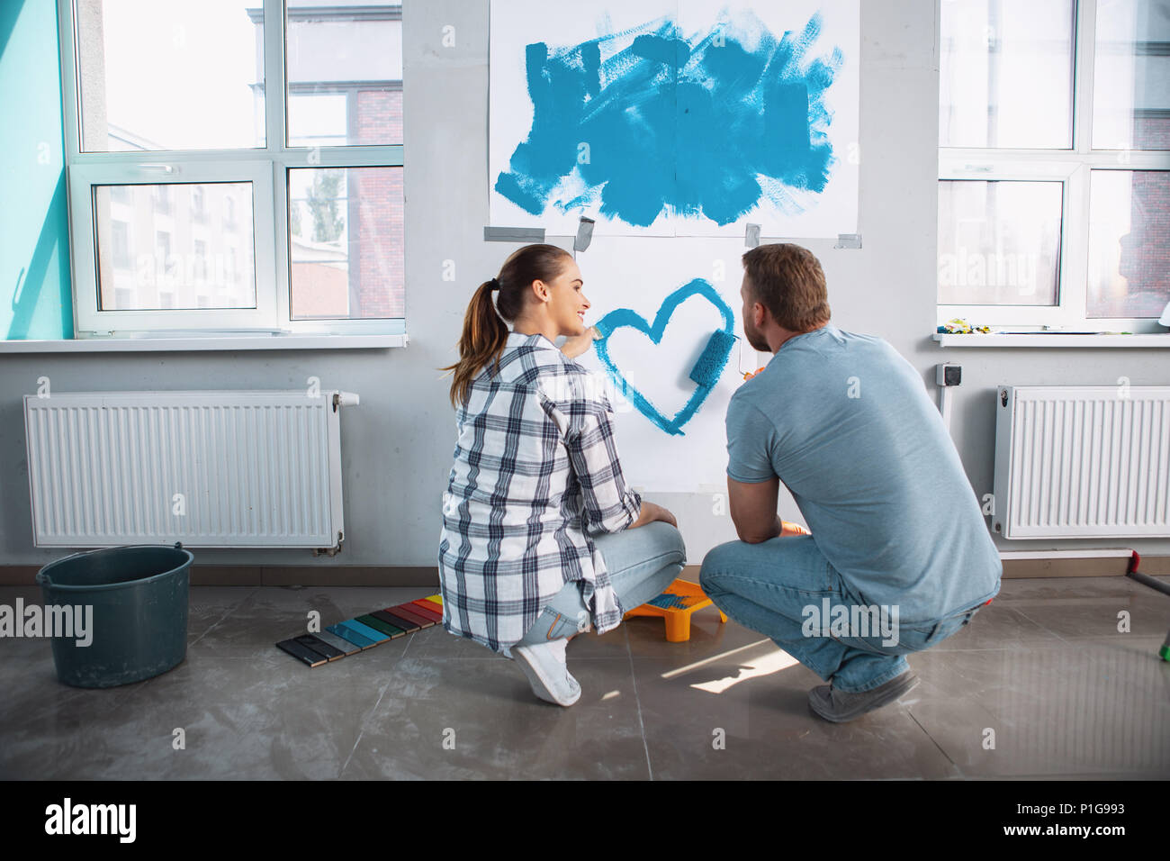Cheerful loving woman painting a heart for her man - Stock Image