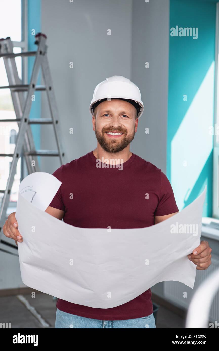 Inspired builder holding a big sketch - Stock Image