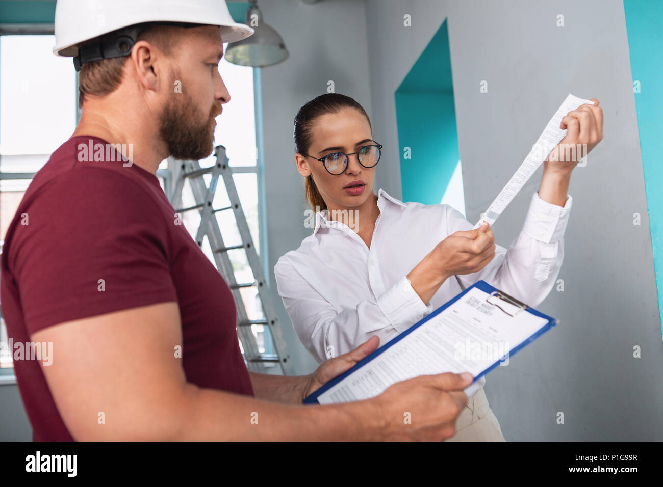 Serious businesswoman holding a building cheque - Stock Image
