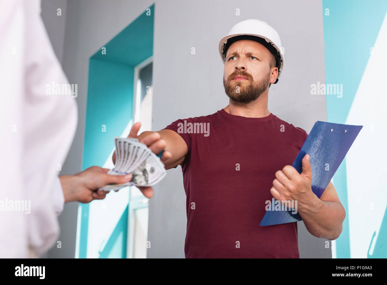 Indignant builder refusing to take a bribe - Stock Image
