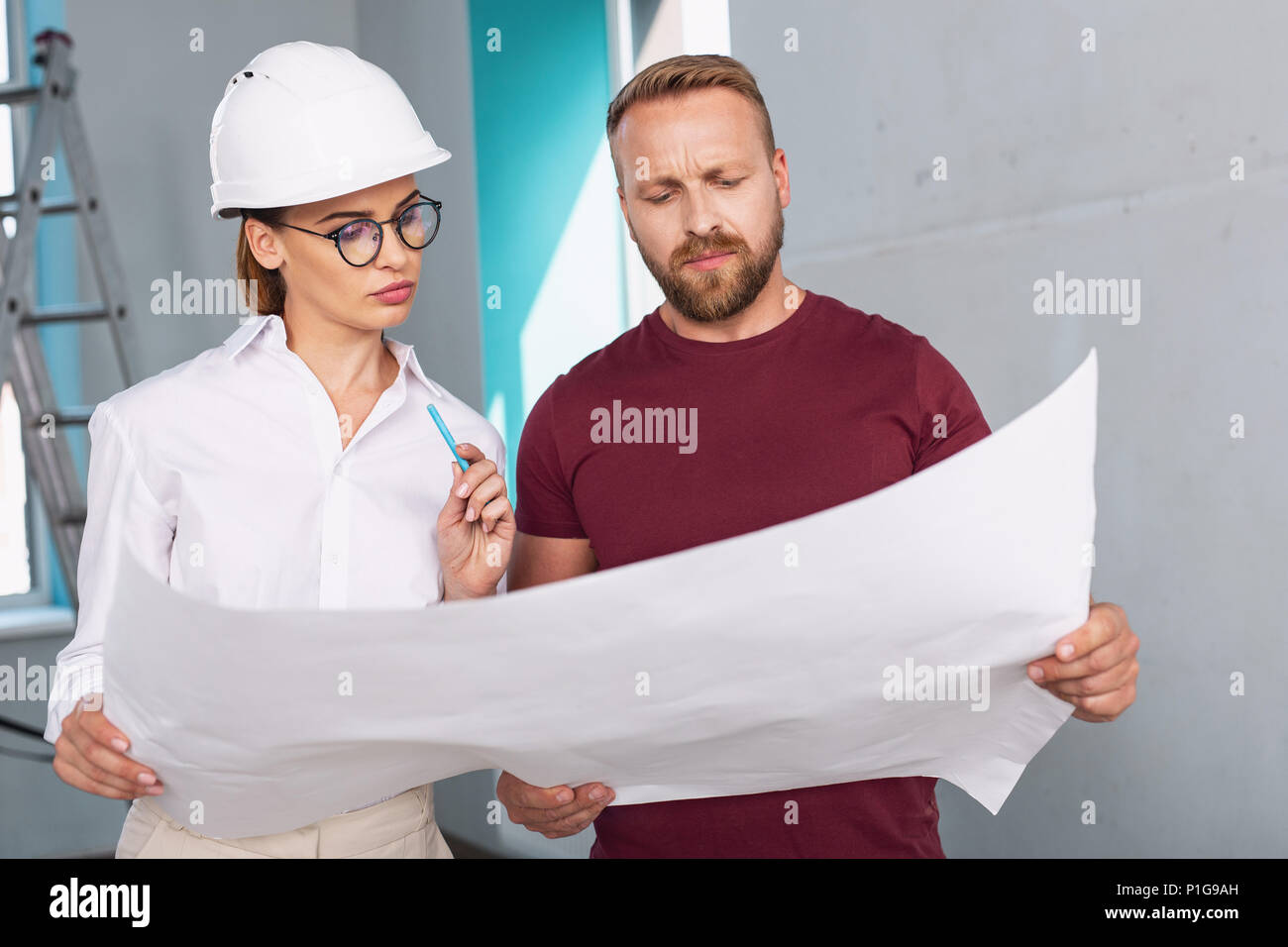Unsmiling designer and client talking about the project - Stock Image