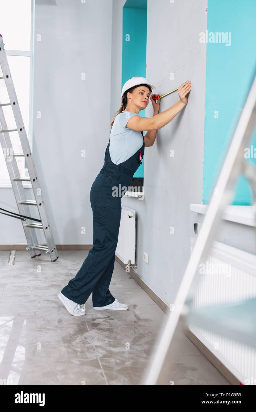 Inspired builder holding a measuring tape Stock Photo