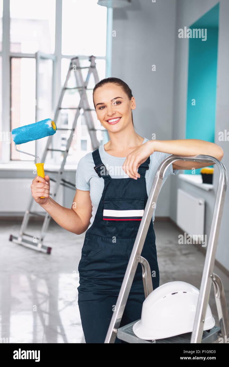 Smiling female builder holding a roller - Stock Image