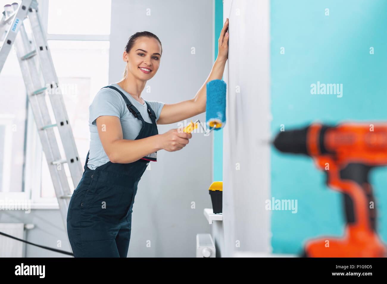 Exuberant female builder holding a roller - Stock Image