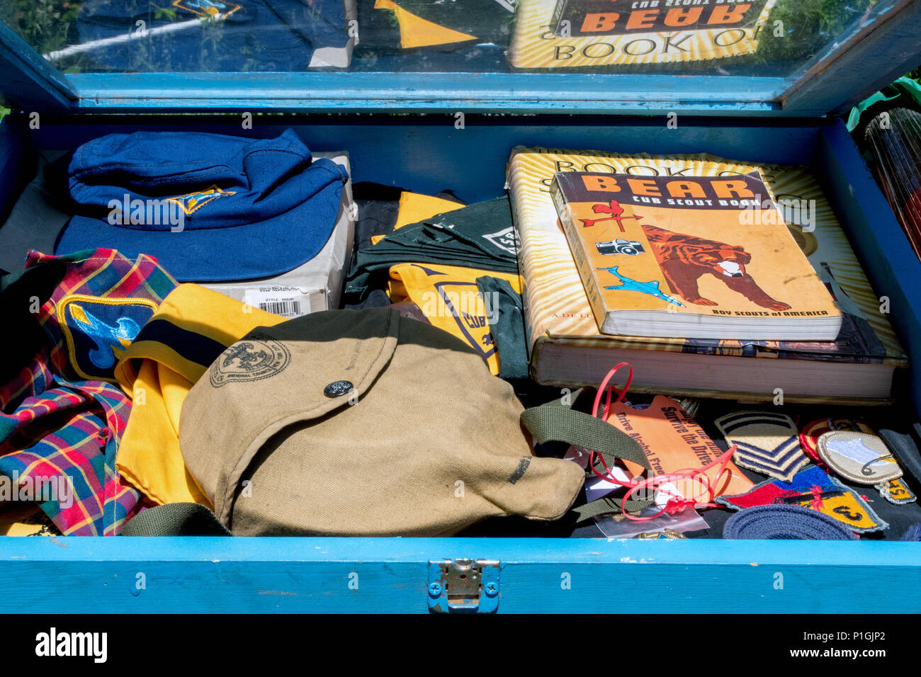 a box of rare old boy scout items are a treasure trove for a collector. scouting uniform, badges, books and caps, beautifully preserved - Stock Image