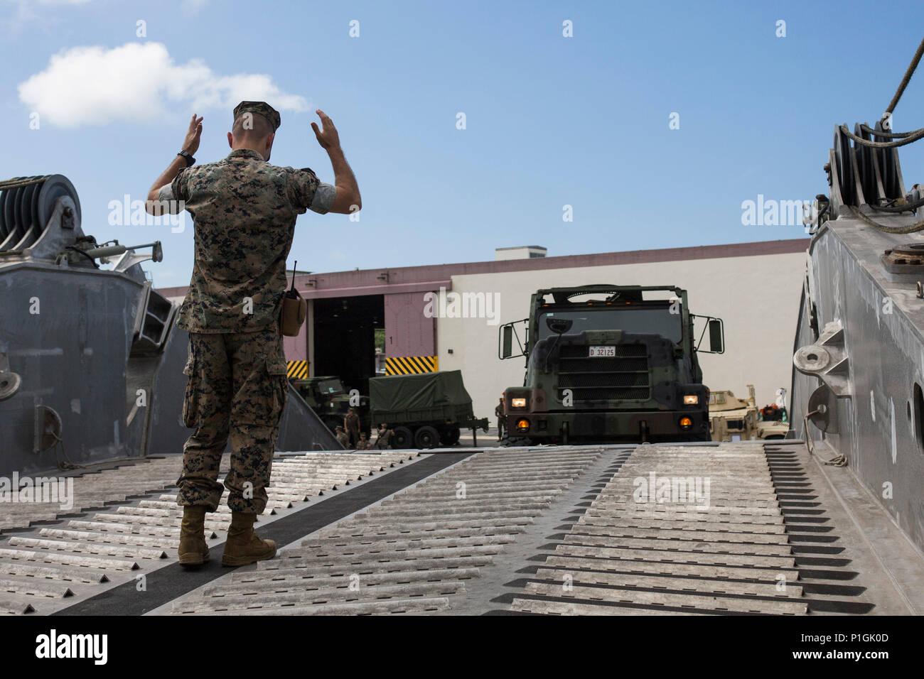Cpl. Tyler Odeneal guides a 7-ton truck up a ramp to embark the USNS Fall River (T-EPF-4) at Naha Port, Okinawa, Japan during Blue Chromite 2017, October 28, 2016. Blue Chromite is a U.S. – only exercise which strengthens the Navy-Marine Corps expeditionary, amphibious rapid-response capabilities based in Okinawa and the greater Indo-Asia-Pacific region. Odeneall, from Hopedale, Illinois, is a motor transportation operator with Truck Company, 3rd Marine Division, Headquarters Battalion, III Marine Expeditionary Force. (U.S. Marine Corps photo by MCIPAC Combat Camera Lance Cpl. Tiana Boyd) - Stock Image