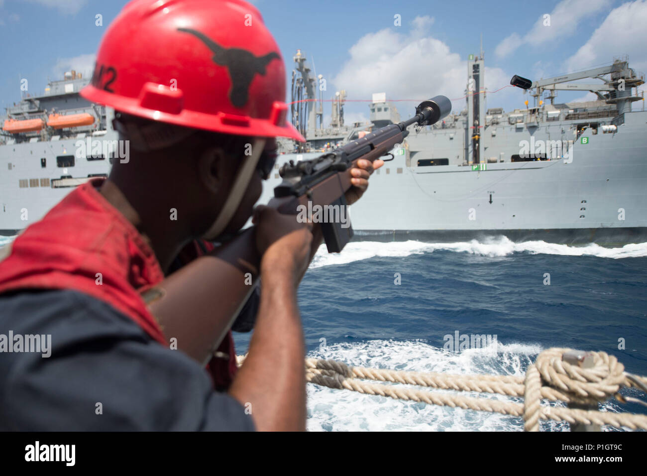 161026-N-DQ503-010  ARABIAN SEA (Oct. 26, 2016) Petty Officer 2nd Class Allen Marshall fires a shot line from the guided-missile destroyer USS Roosevelt (DDG 80) to the fleet replenishment oiler USNS Laramie (T-AO 203) during a replenishment-at-sea. Roosevelt, deployed as part of the Eisenhower Carrier Strike Group, is supporting maritime security operations and theater security cooperation efforts in the U.S. 5th Fleet area of operations. (U.S. Navy photo by Petty Officer 3rd Class Taylor A. Elberg) - Stock Image