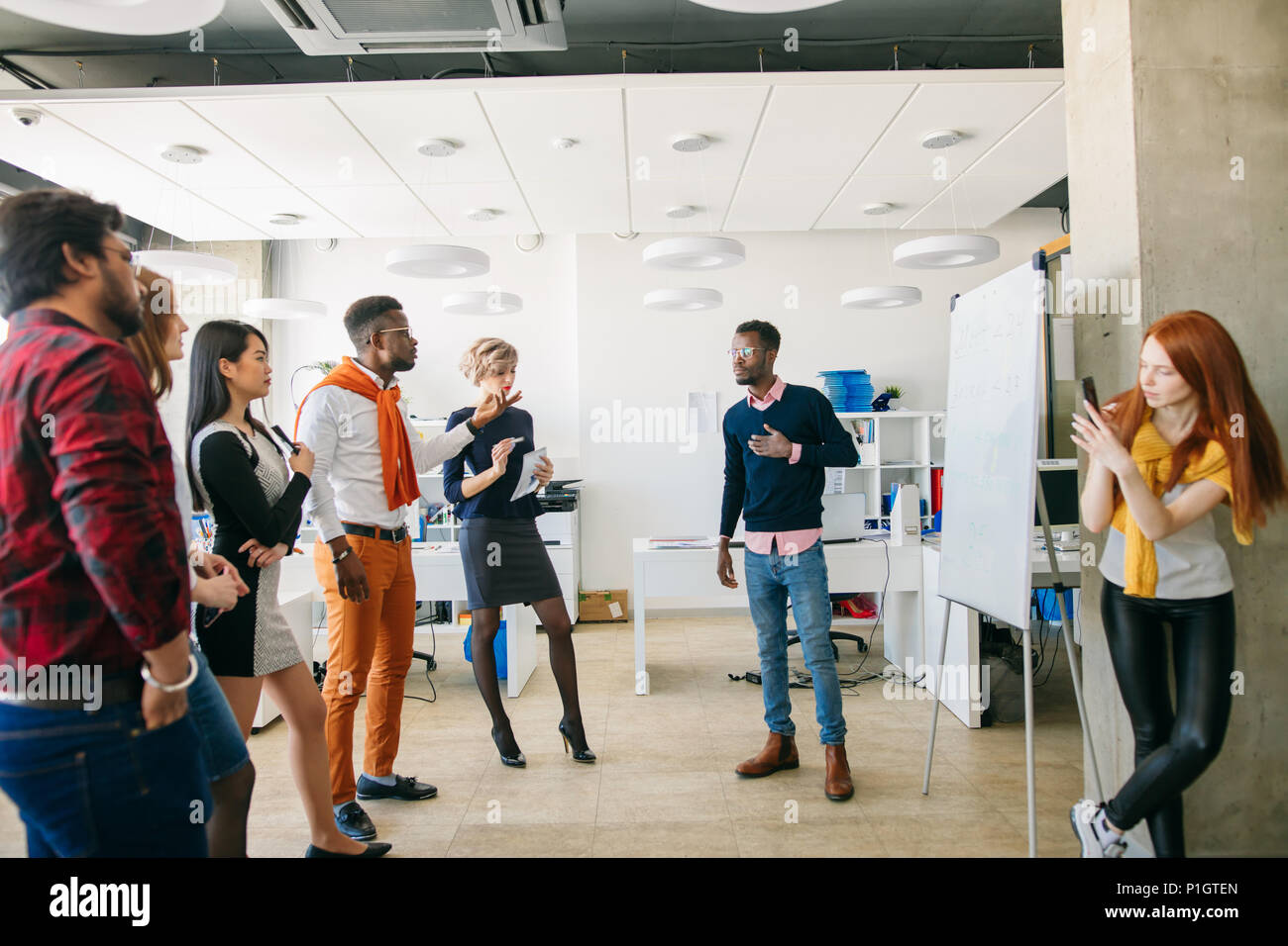 african man in white T-shirt and orange trousers and his team asking question - Stock Image
