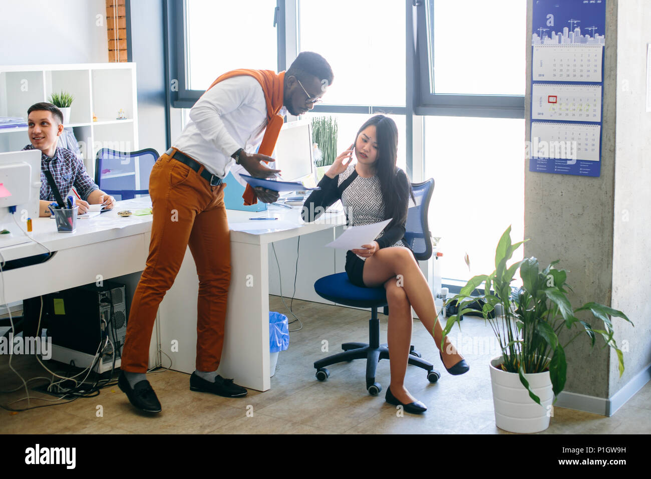 Asian woman is showing document to african assistant while talking on smartphone - Stock Image