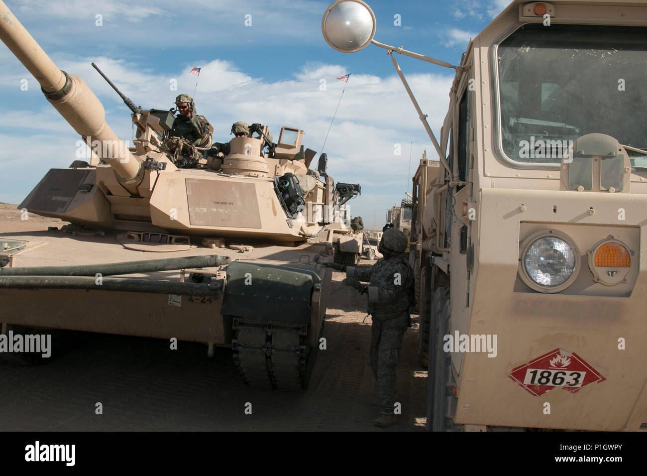 U.S. Soldier M1A2 Abrams tank crews from the 3rd Battalion, 8th Cavalry Regiment, 3rd Armored Brigade Combat Team, 1st Cavalry Division roll through a fuel point during the live-fire portion of the brigade's during National Training Center 17-01 at Fort Irwin, Calif., Oct. 13, 2016. NTC 17-01 provides U.S. military units and personnel with realistic pre-deployment training scenarios in all aspects of armed conflict. (U.S. Army photo by Staff Sgt. Leah Kilpatrick) Stock Photo
