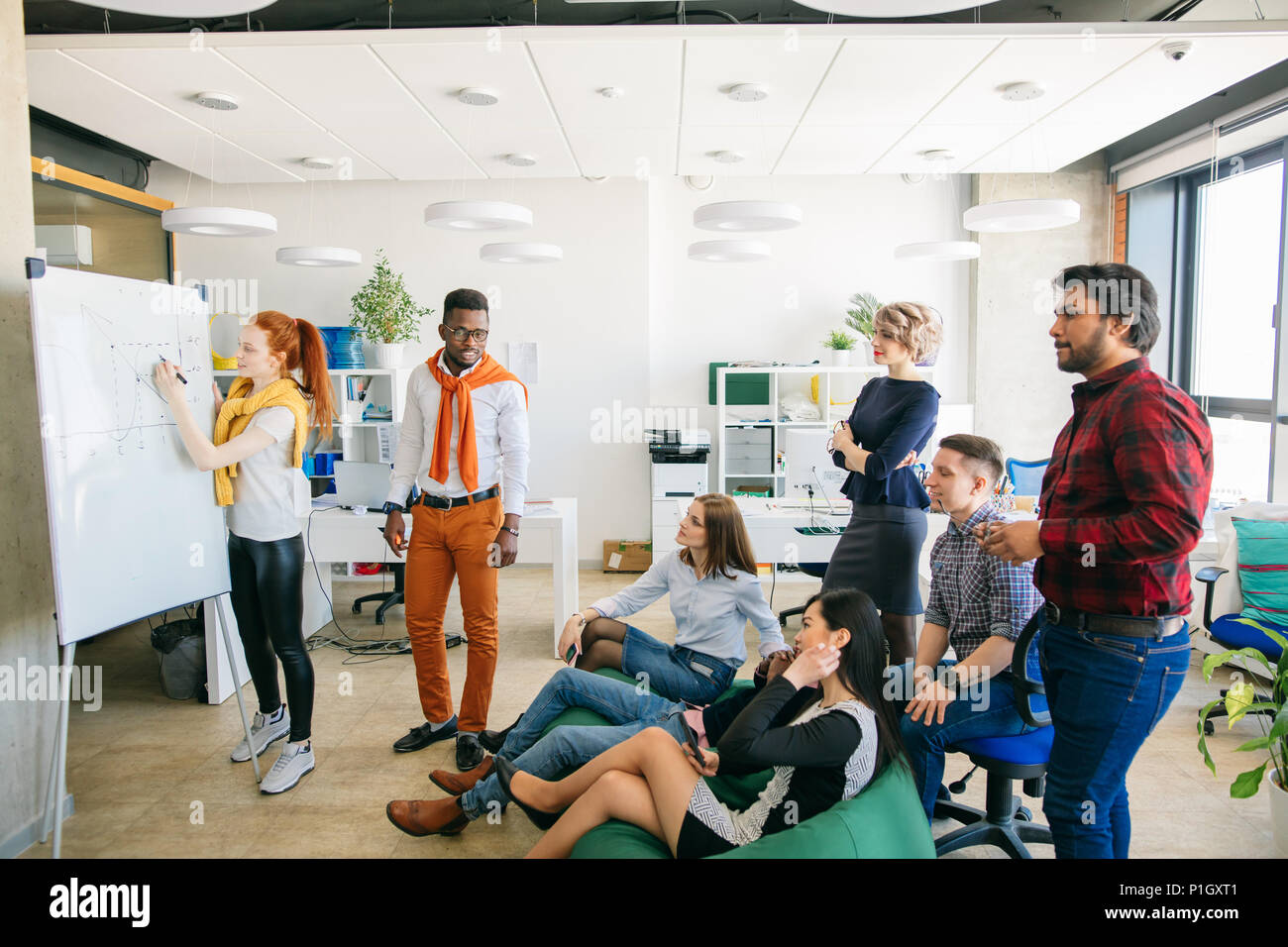 team in casual clothes looking at the ginger female writing chart on whiteboard - Stock Image