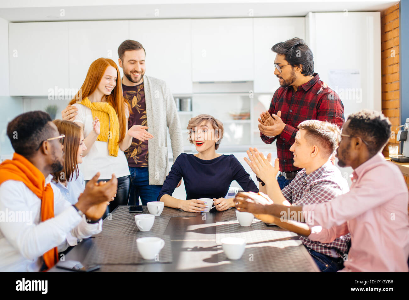 employees enjoying spending time togeter while drinking coffee - Stock Image