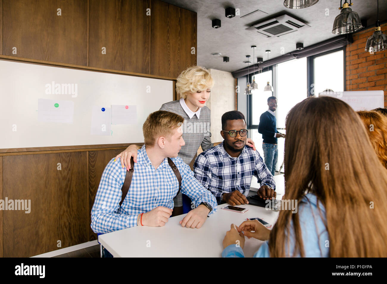 attractive female boss standing between her male workers - Stock Image