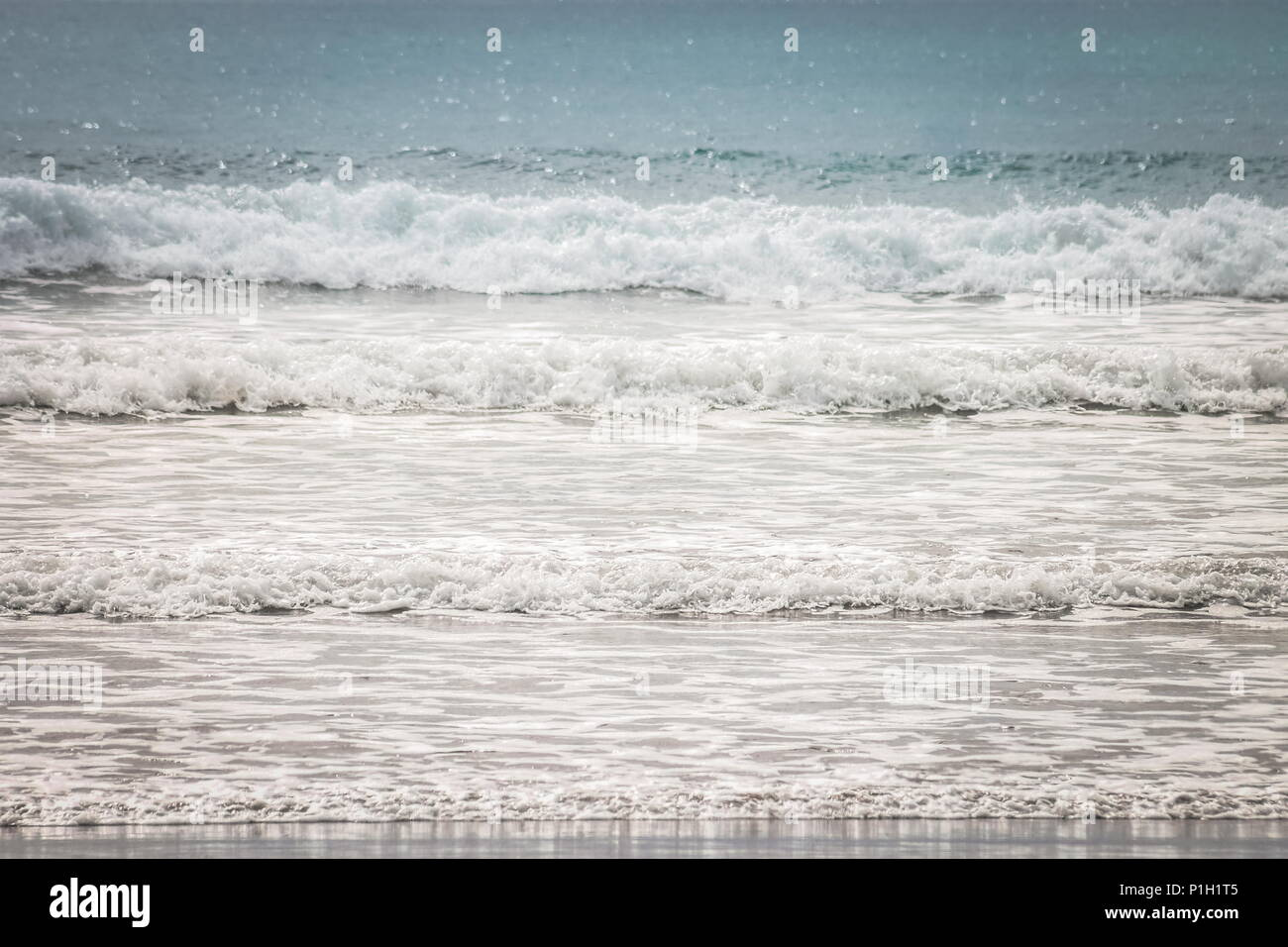 Background image of Gentle waves rolling on to shore - Stock Image