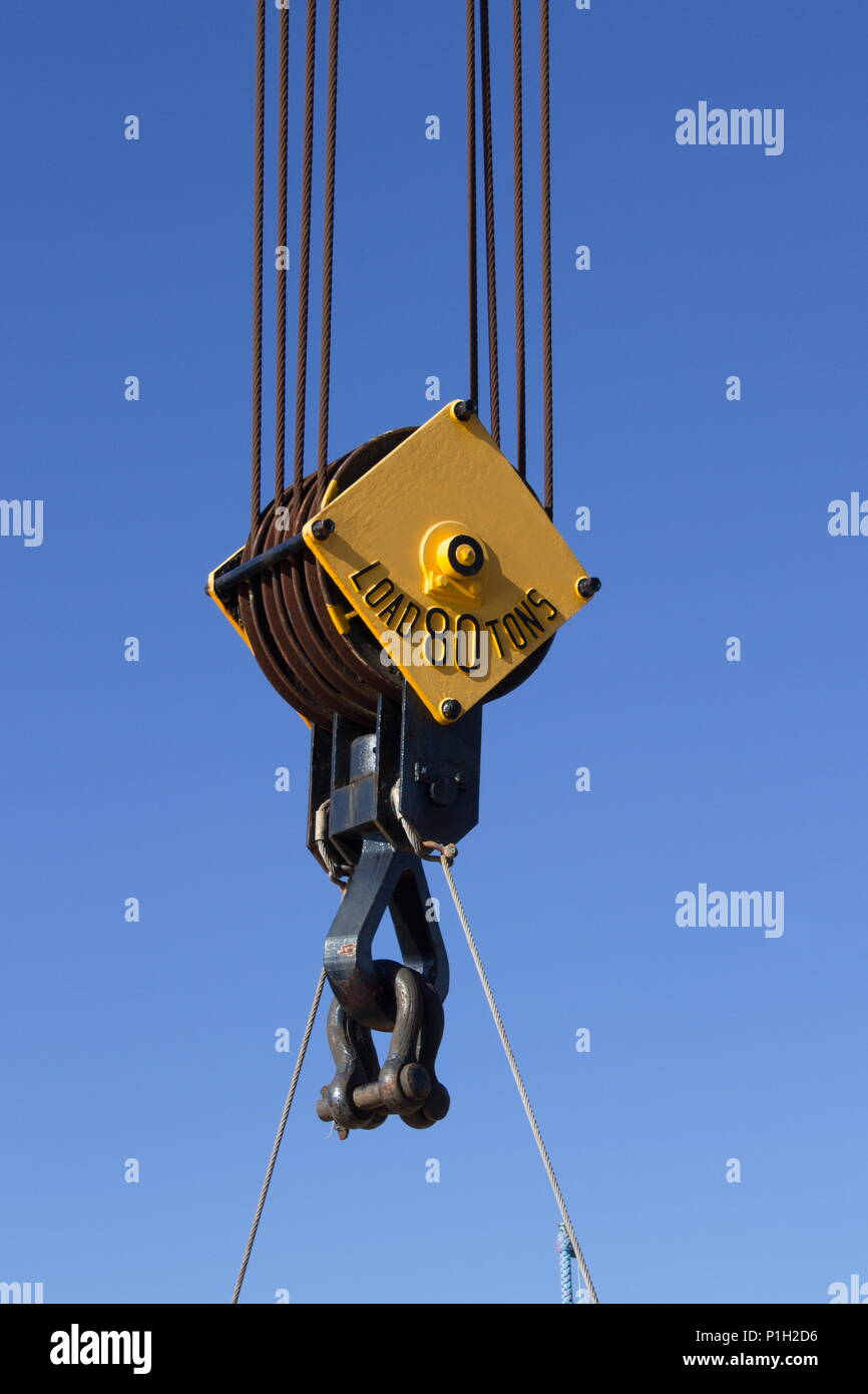 Close up image of a steel cable pulley on  a crane against a blue sky. - Stock Image