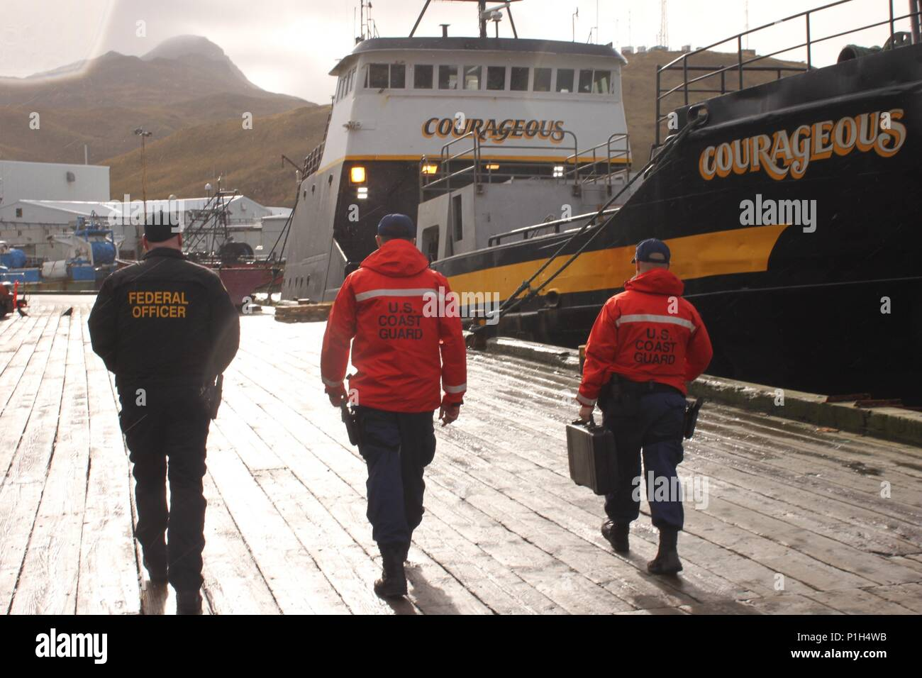 NOAA OLE Officer Roy Fisher, Ensign Nolan Salyer and Petty Officer 3rd Class Thomas Labarre, a maritime enforcement specialist, conduct joint agency boarding of the fishing vessel Courageous that previously served as the Coast Guard buoy tender Tupelo before being decommissioned, in Dutch Harbor, Alaska, Oct. 28, 2016. The Morgenthau conducted a 90-day 15,000 mile patrol in support of fisheries enforcement and served as a search and rescue asset during the busy Alaska fishing seasons. (U.S. Coast Guard photo by Ensign Brandon Newman/Released) - Stock Image