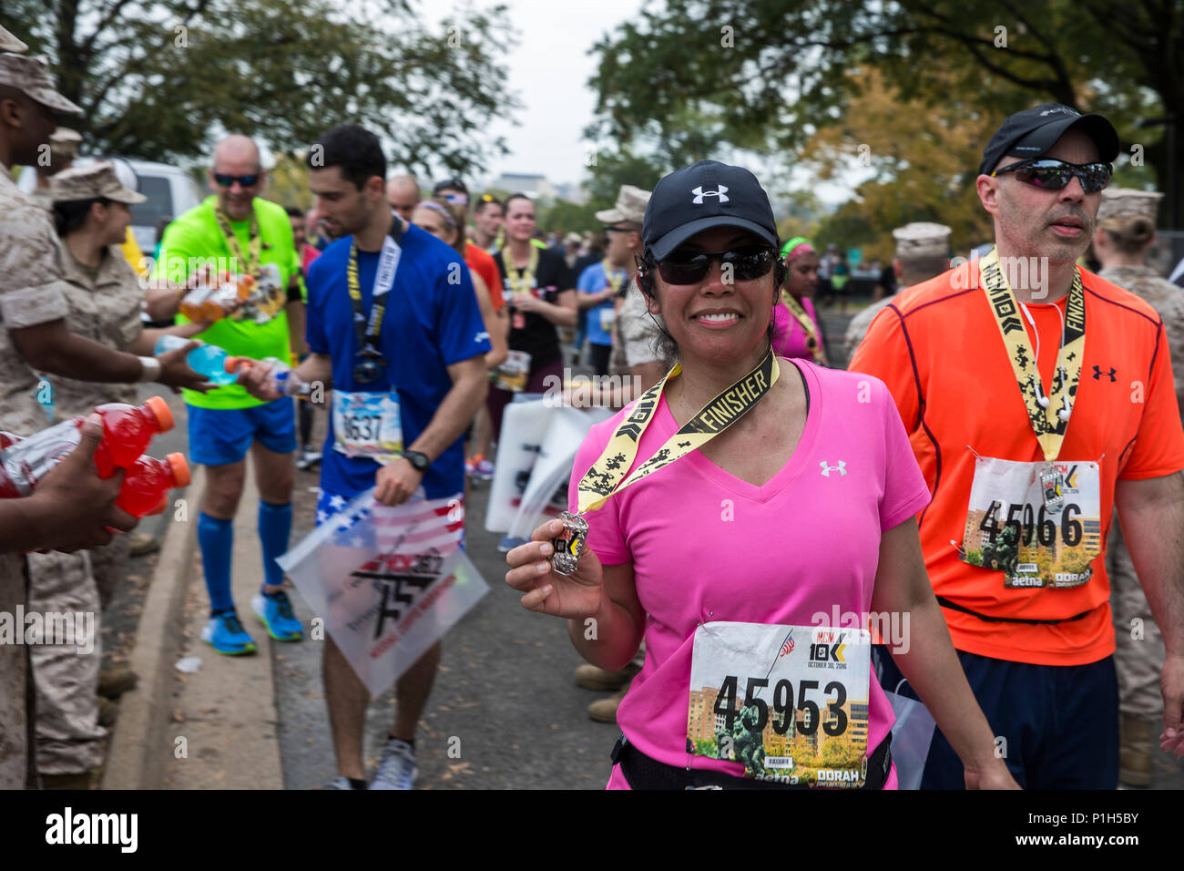 "Mirasol Espanola shows off the medal she received for finishing the 41st Marine Corps Marathon 10k, Arlington, Va., Oct. 30, 2016. Also known as ""The People's Marathon,"" the 26.2 mile race drew roughly 30,000 participants to promote physical fitness, generate goodwill in the community, and showcase the organizational skills of the Marine Corps. (U.S. Marine Corps photo by Lance Cpl. Alexander Cockrell) Stock Photo"