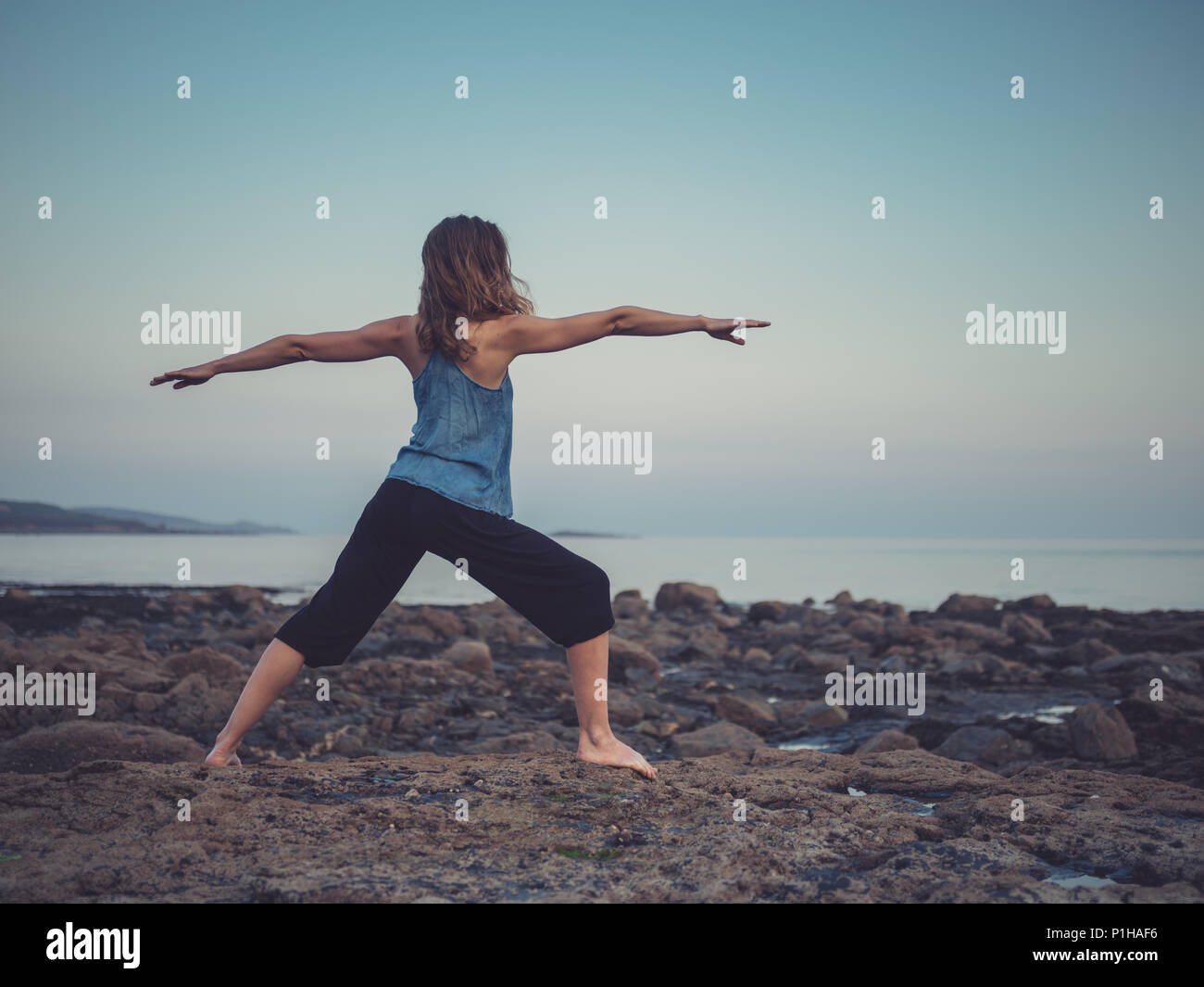 A young woman is doing yoga on the coast at sunset and is standing in a warrior pose - Stock Image