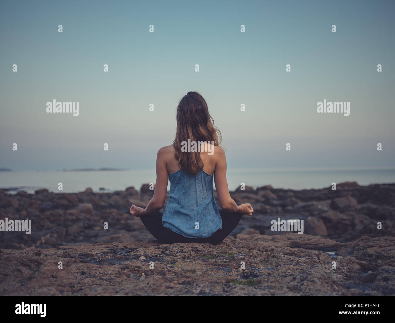 A young woman is sitting on the rocks by the sea at sunset meditating - Stock Image