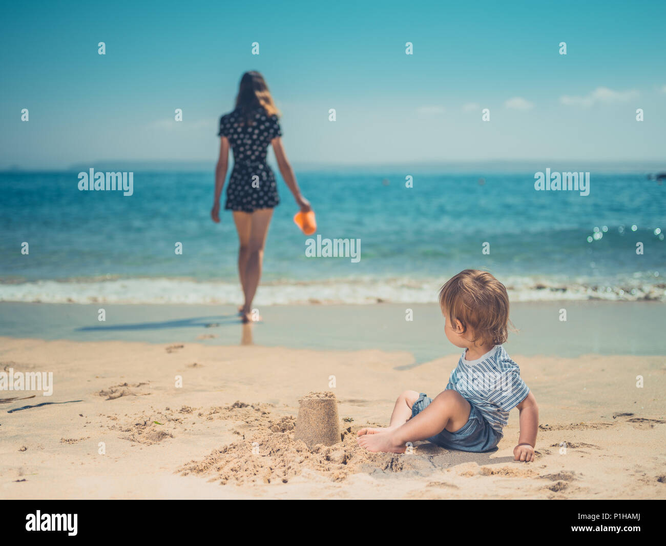A young mother is playing with her son on the beach, building sand castles - Stock Image