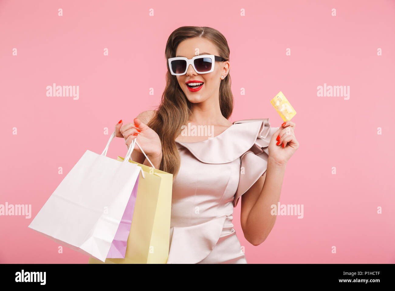 a008cebf78d65 Photo of stylish woman in dress and sunglasses smiling while holding  different shopping bags and credit card in hands isolated over pink  background
