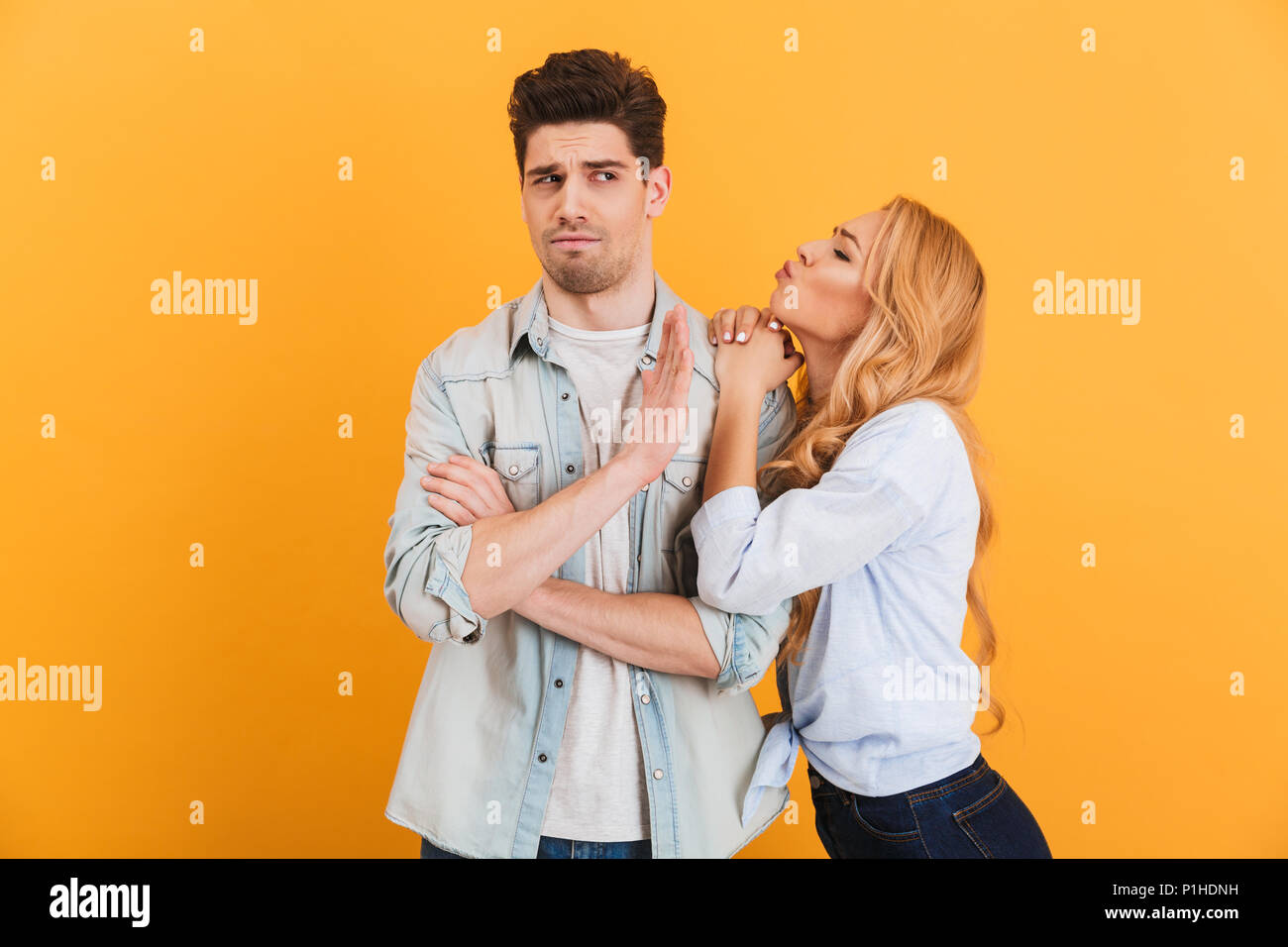 Portrait of young displeased man gesturing to stop with hand while beautiful woman kissing his cheek isolated over yellow background - Stock Image