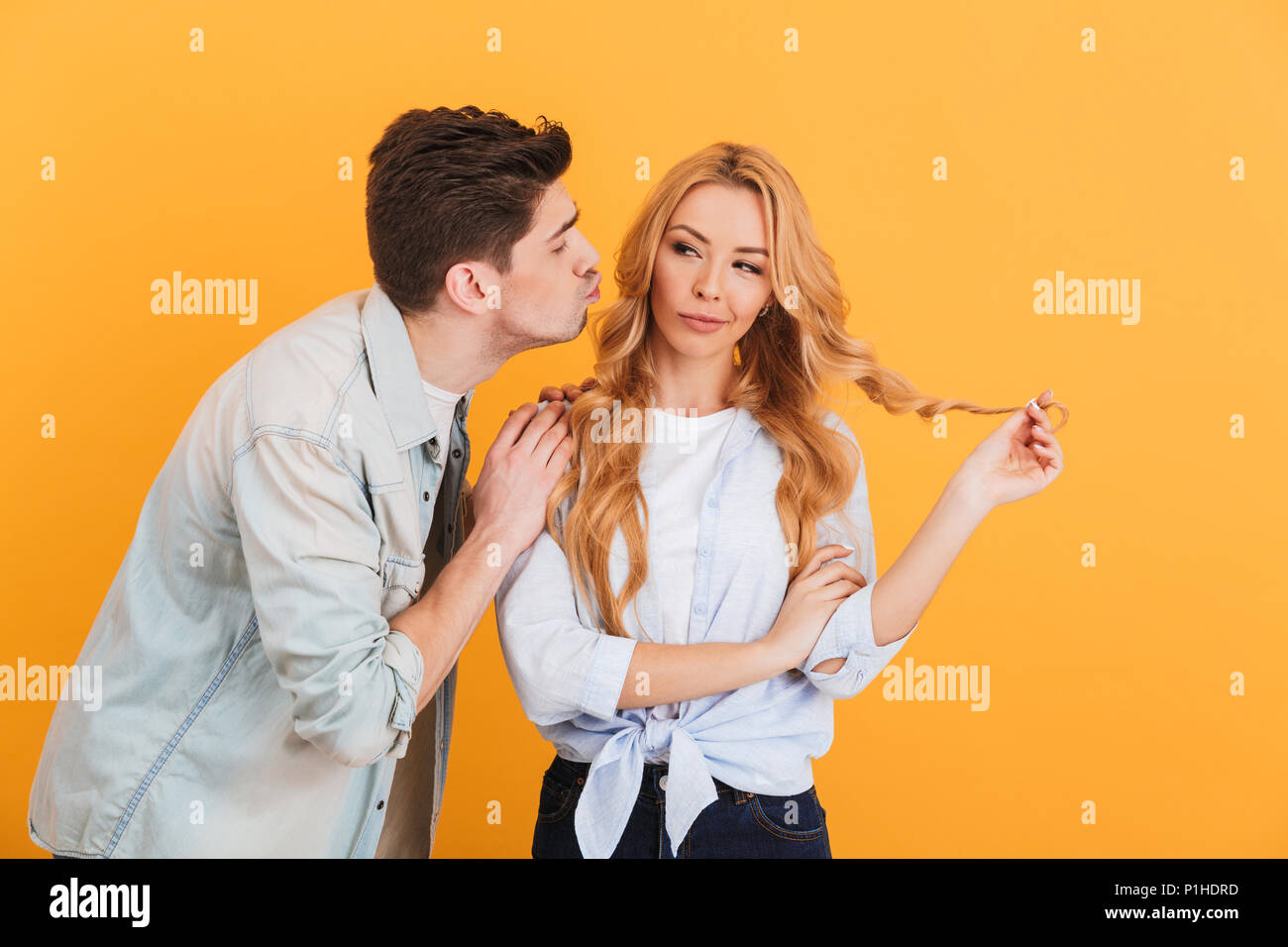 Portrait of charming woman looking aside and hesitating while man trying to kiss her cheek isolated over yellow background - Stock Image