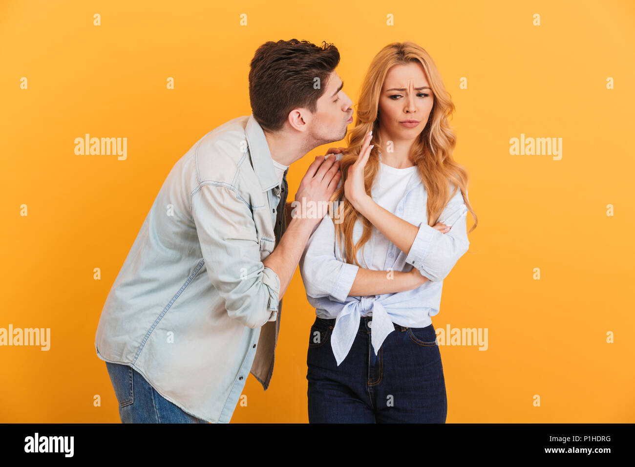 Portrait of outraged displeased woman gesturing to stop with hand while man trying to kiss her isolated over yellow background - Stock Image