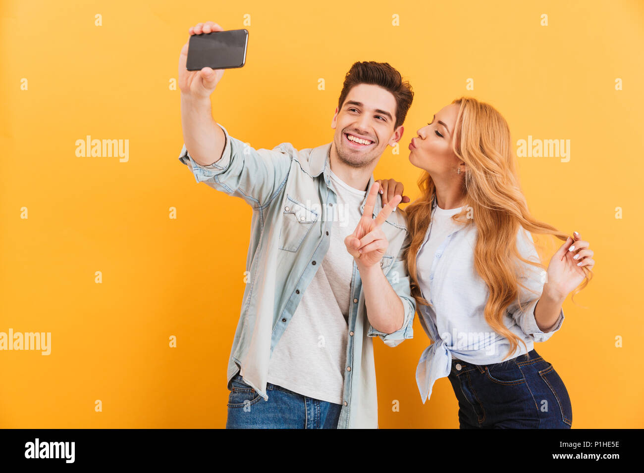 Portrait of lovely couple taking selfie photo on cell phone while woman kissing man on his cheek isolated over yellow background - Stock Image